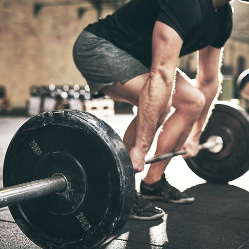 a man is squatting and lifting barbells
