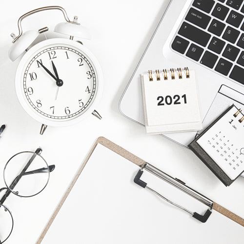 a clock, a laptop, notebook with 2021 new year resolutions