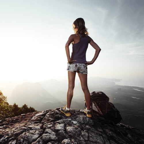 a woman is standing at the top of mountain