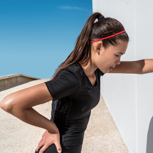 a woman is relying on a wall after working out