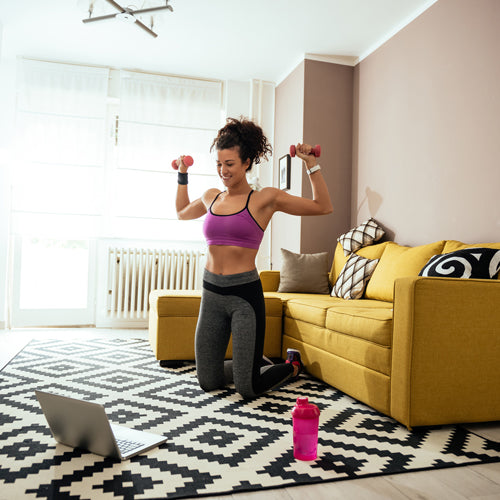 a woman is doing dumbbell workout in living room