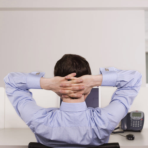 an office man is putting hands on his head and watching his laptop