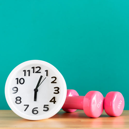an alarm and two pink dumbbells