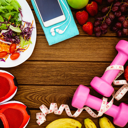 pink dumbbell with phone and a bowl of salad