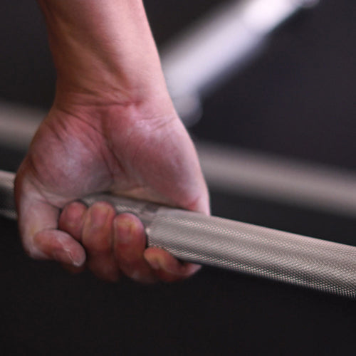 a hand is holding olympic bar