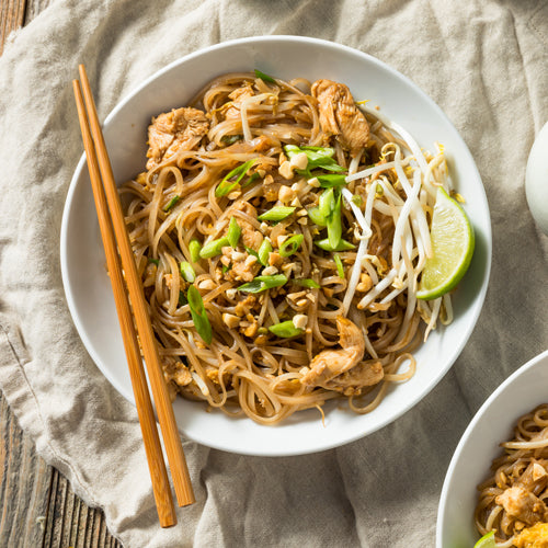 a bowl of chicken pad thai