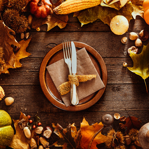 a bowl with knife and fork on a fall feeling decorated table