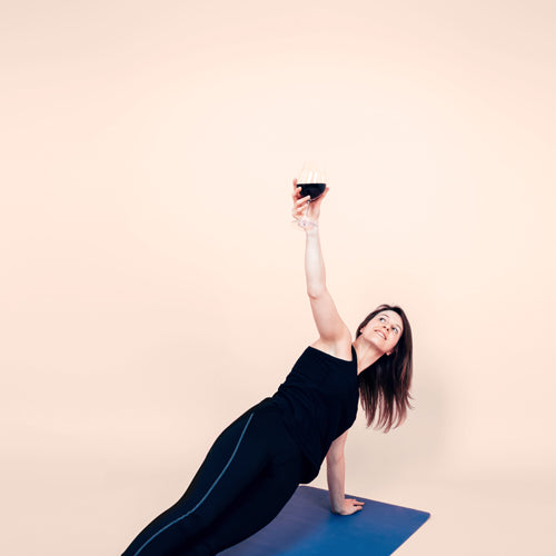 a woman is holding a wine glass and working out