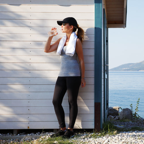 a woman is drinking water after exercising outdoors