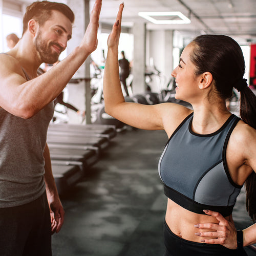 man and woman doing a high-five in gym