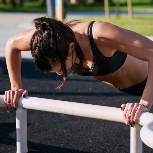 a female athlete is pushing up outdoors