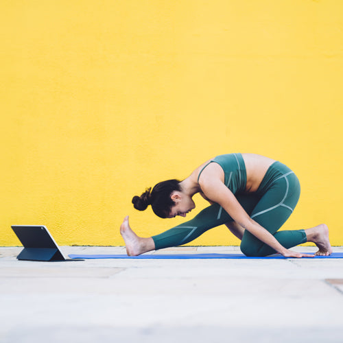 a lady is stretching in front of a yellow wall