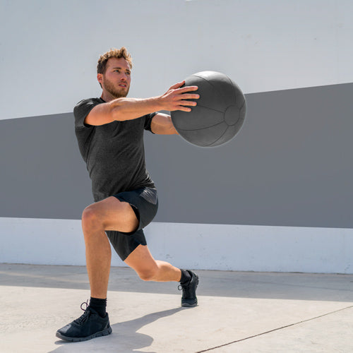 man performing lunge while holding medicinal ball
