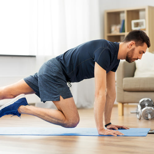 man doing running plank exercise at home