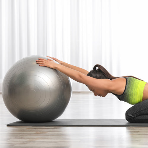 a woman is stretching with gym ball