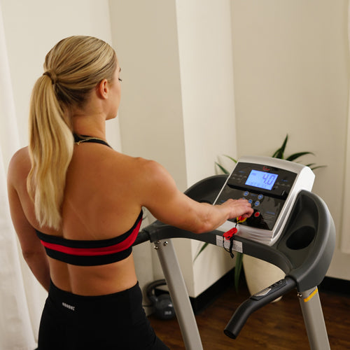 a woman is preparing to run on treadmill