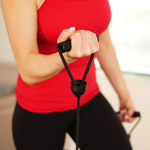 a woman is holding resistance bands