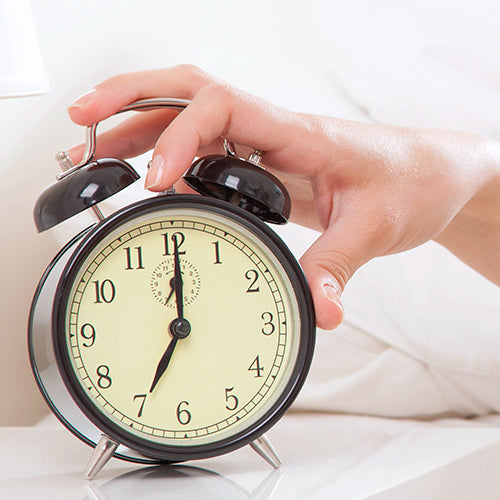 hand turning off alarm clock