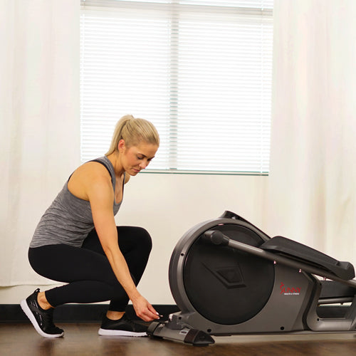 a female exerciser is ready to use an elliptical