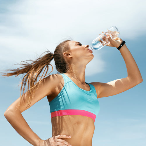 a female athlete is drinking water