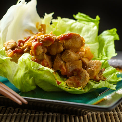 chicken lettuce wrap on a plate with chopsticks