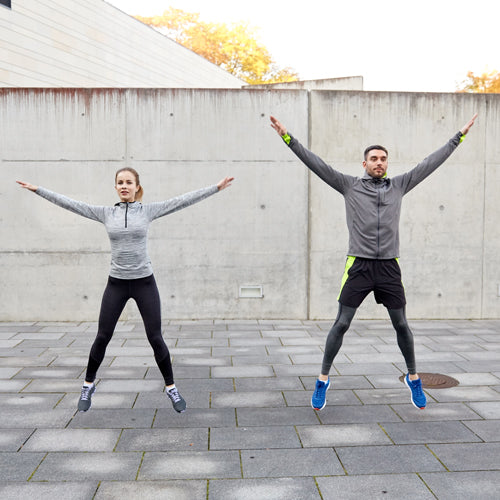 a man and a woman are jumping outdoors