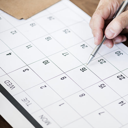 a hand holding a pen on a calendar