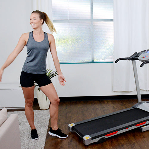 a woman stands beside a treadmill
