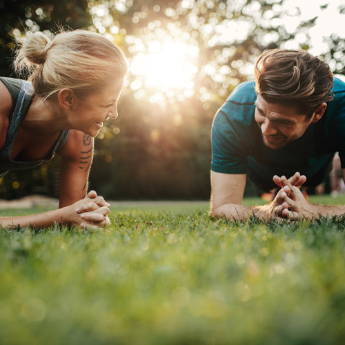 a man and a woman are planking on grass under sunshine