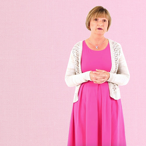 a lady wearing pink dress is talking in front of pink wall