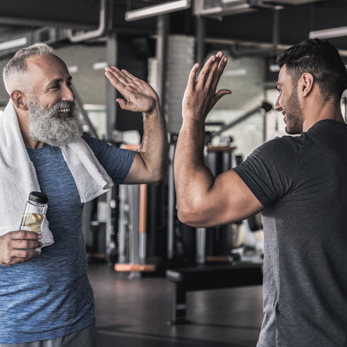 two men are high fiving in the gym