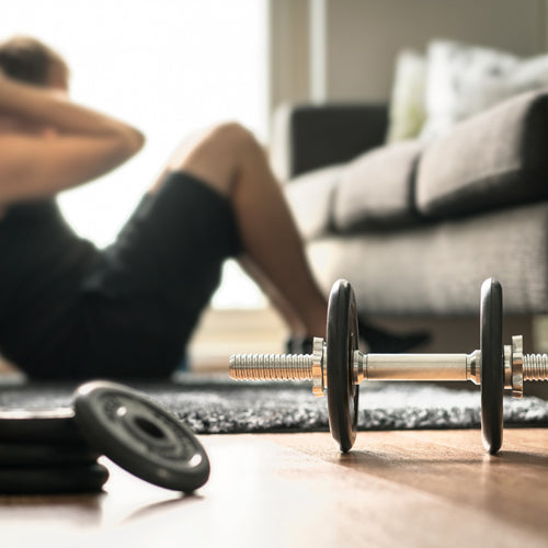 a man is sitting up with dumbbells in living room
