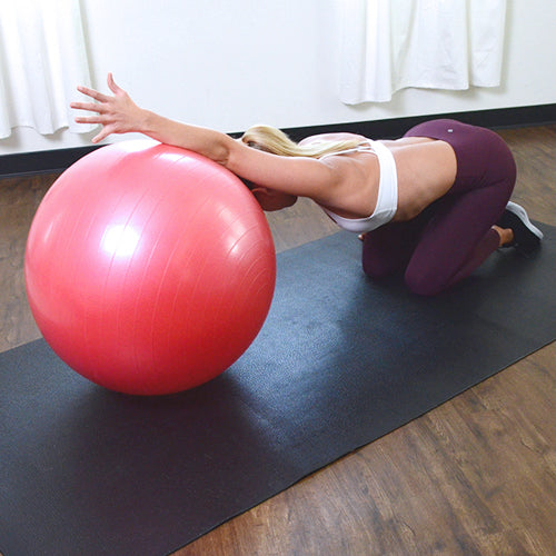 a woman is stretching with the exercise ball