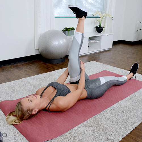a woman is stretching on yoga mat