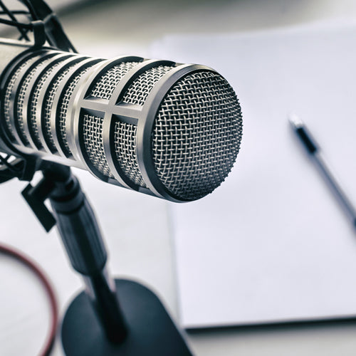 a microphone and a pen on a piece of paper