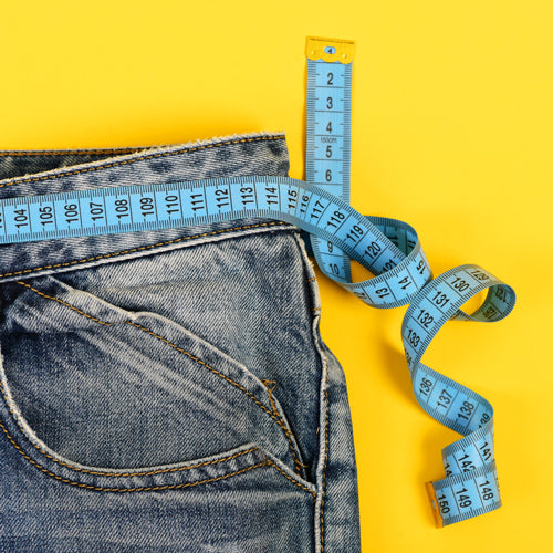 a scale on jeans on the yellow background