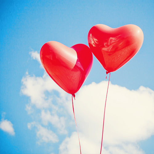 two red heart balloons in sky