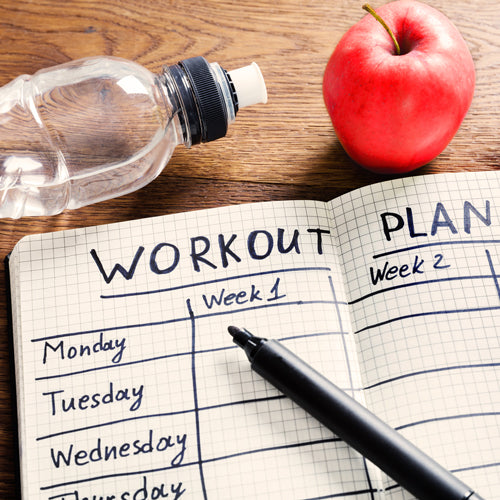 notebook with workout plan, water bottle, apple