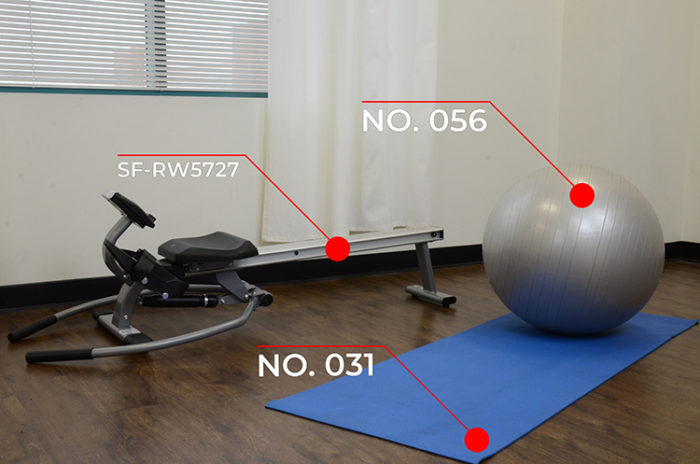 rowing machine, yoga mat, and silver gym ball in room