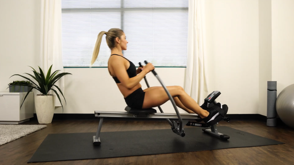 woman rowing with seat in mid position, legs near full extension