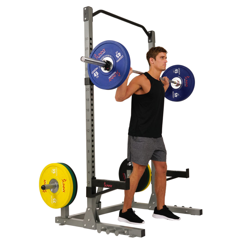 man holding barbell in front of squat rack