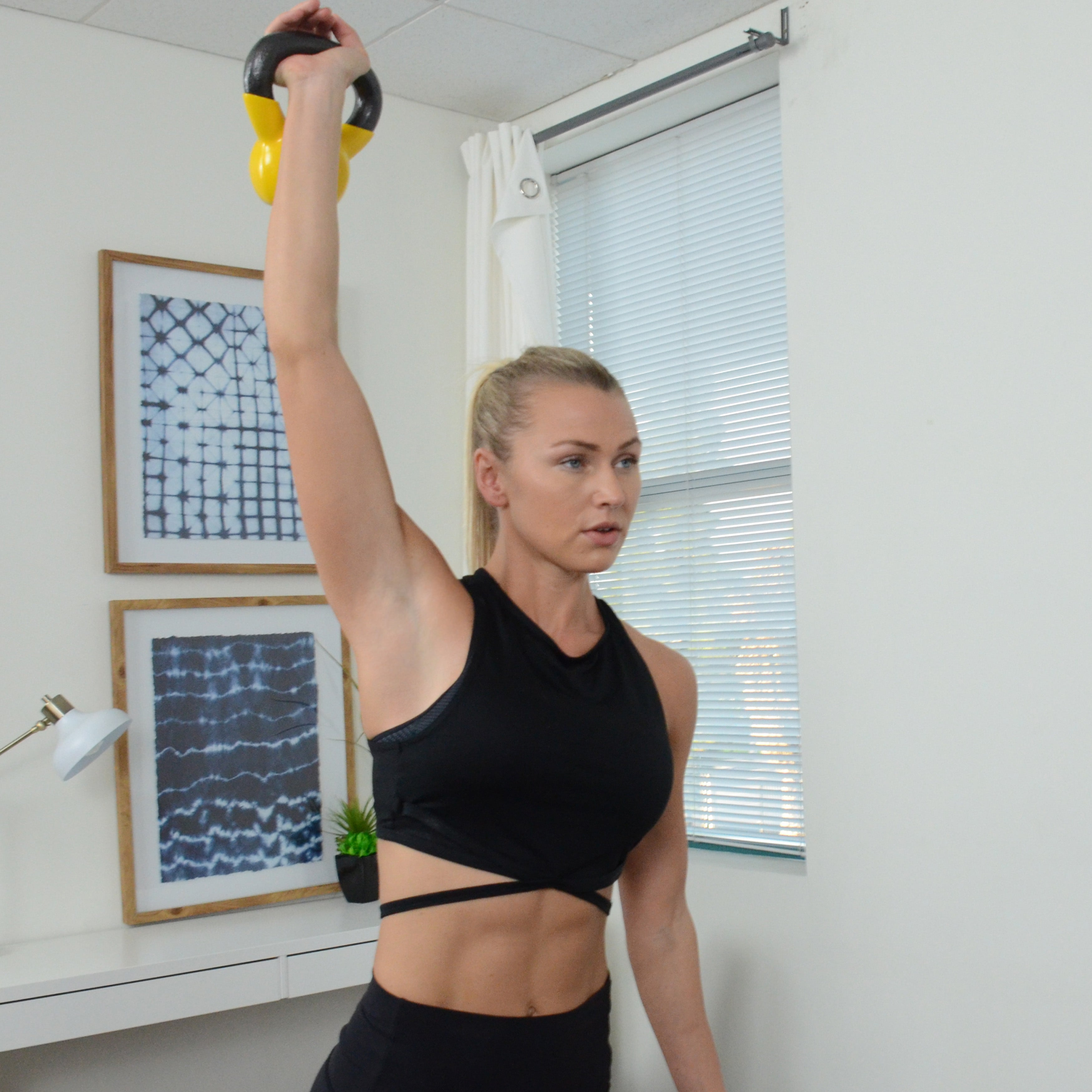 woman raising yellow kettlebell