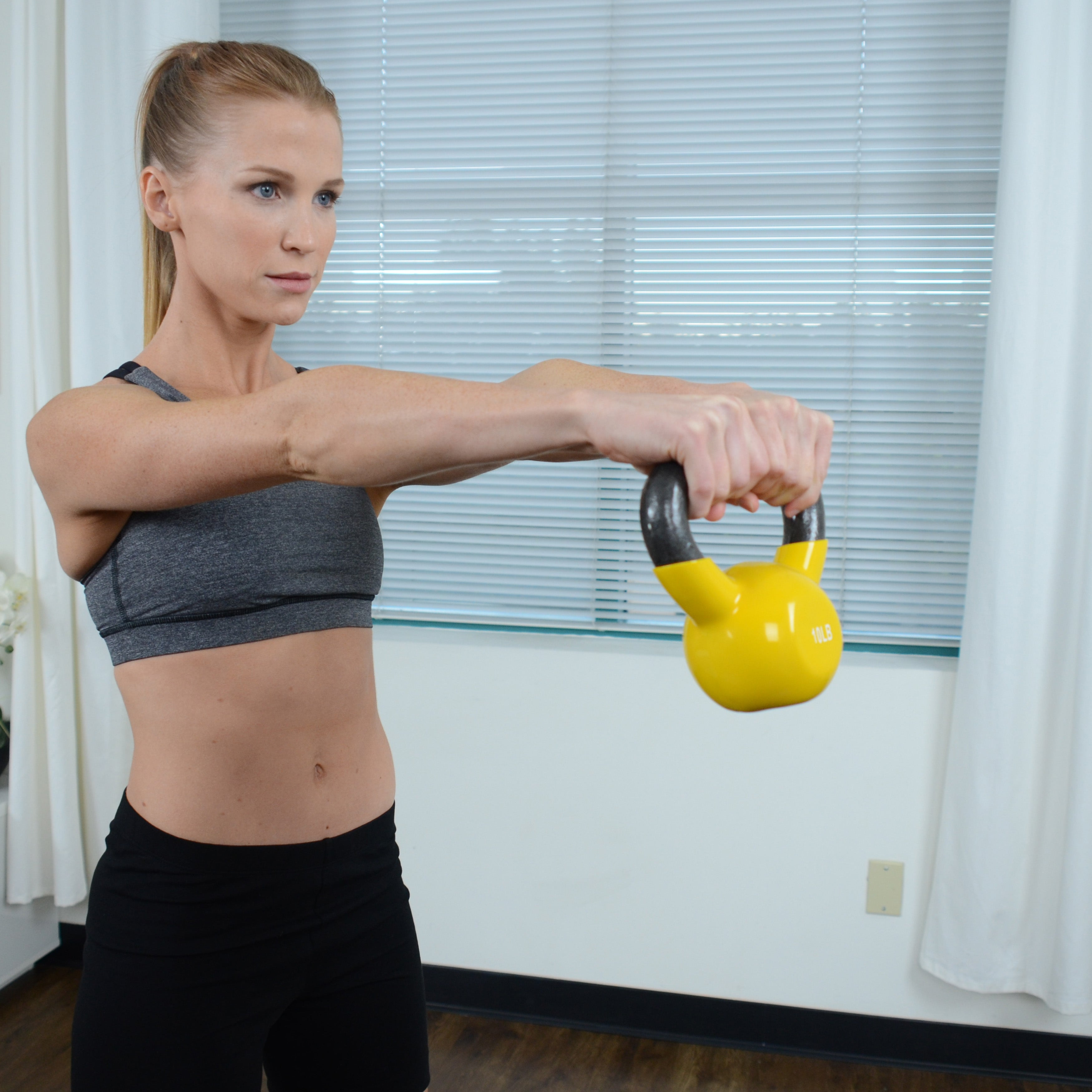 woman holding yellow kettlebell with two hands straight in front of her