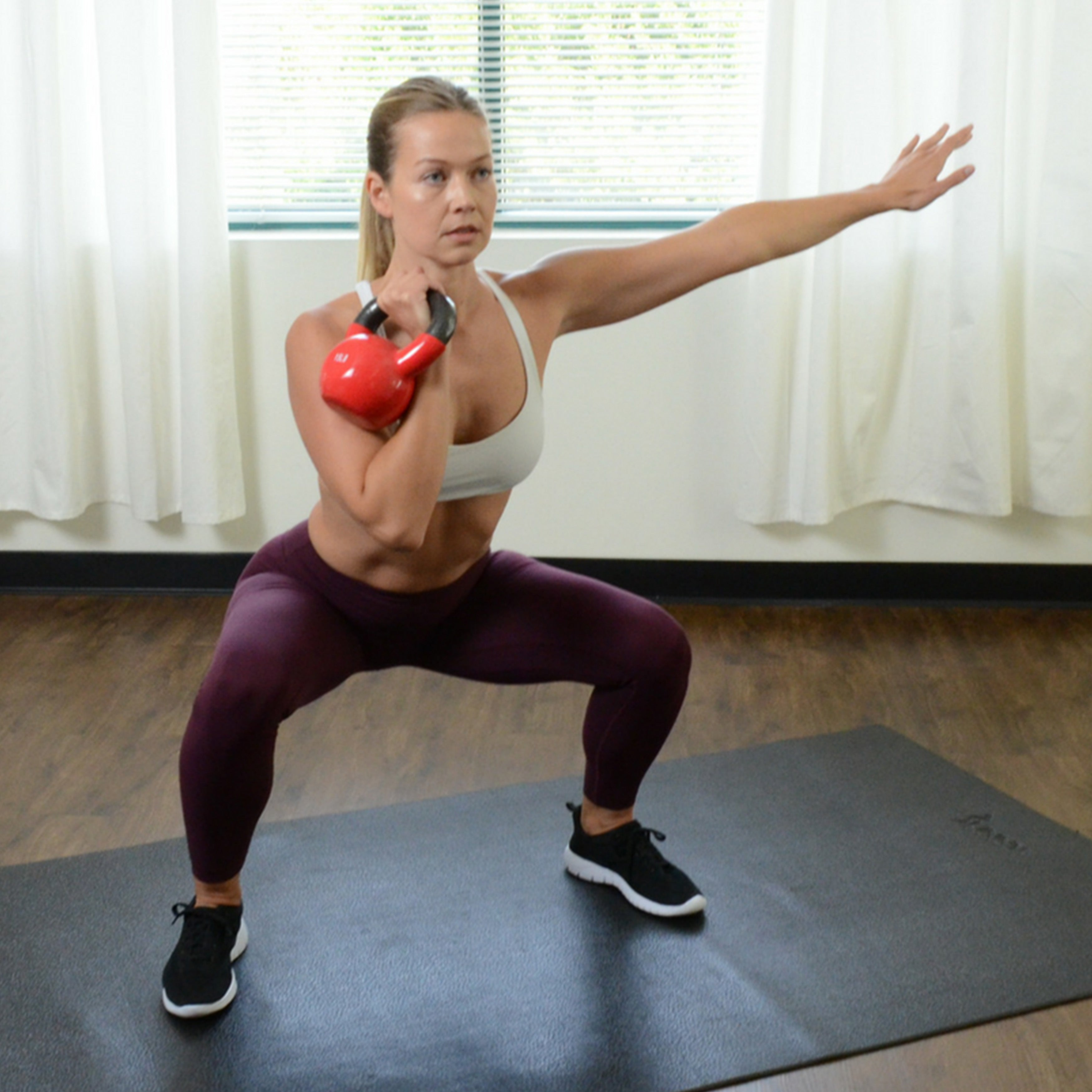 woman holding red kettlebell with her right hand while performing squat