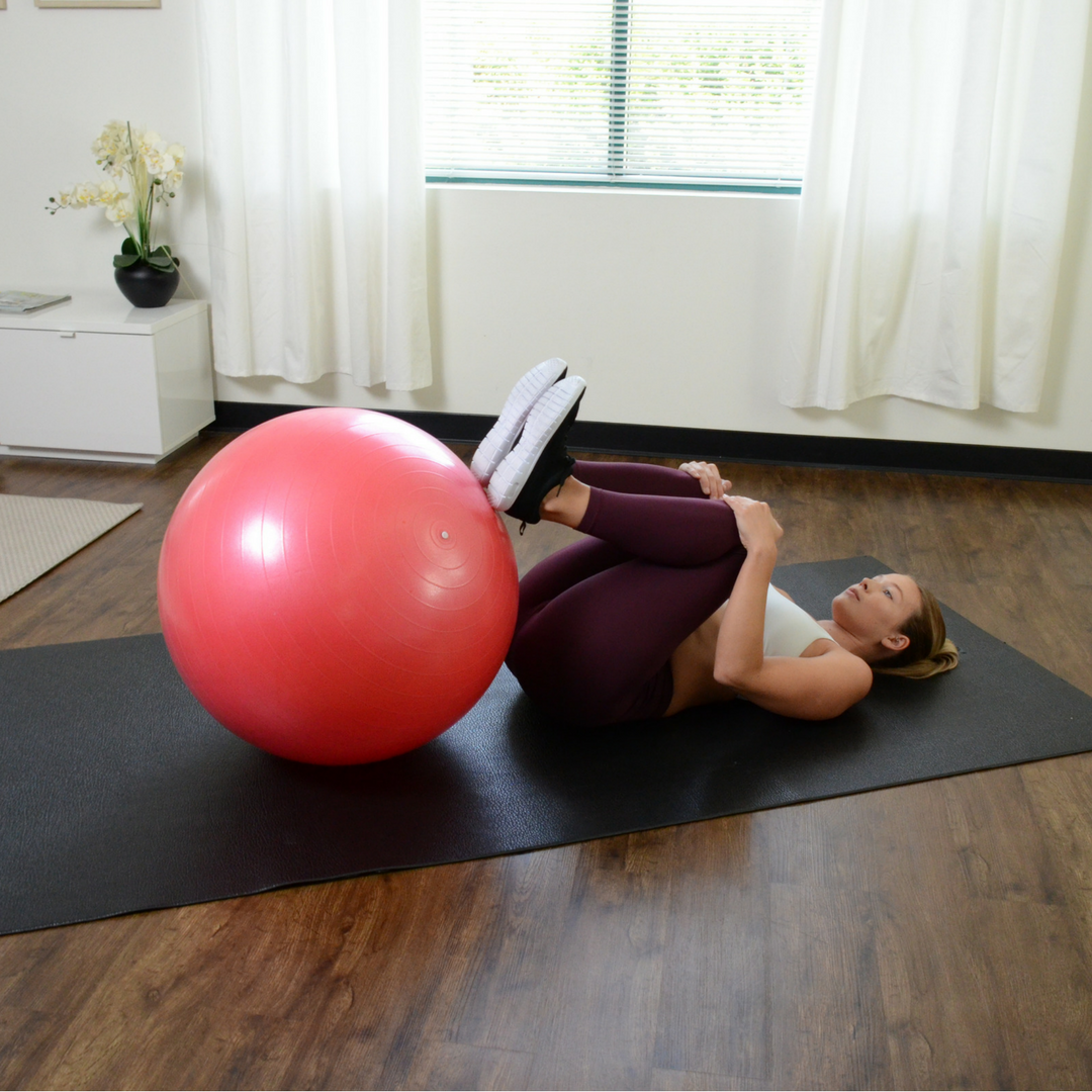 woman laying on back with legs back and feet touching gym ball
