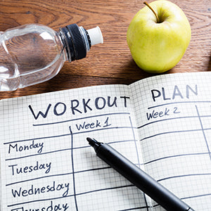 notebook with workout plan and water bottle and green apple on desk with pen