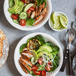 two plates of food containing grilled chicken, grape tomatoes, avocado, spinach, cucumbers with forks and a small plate of lime wedges