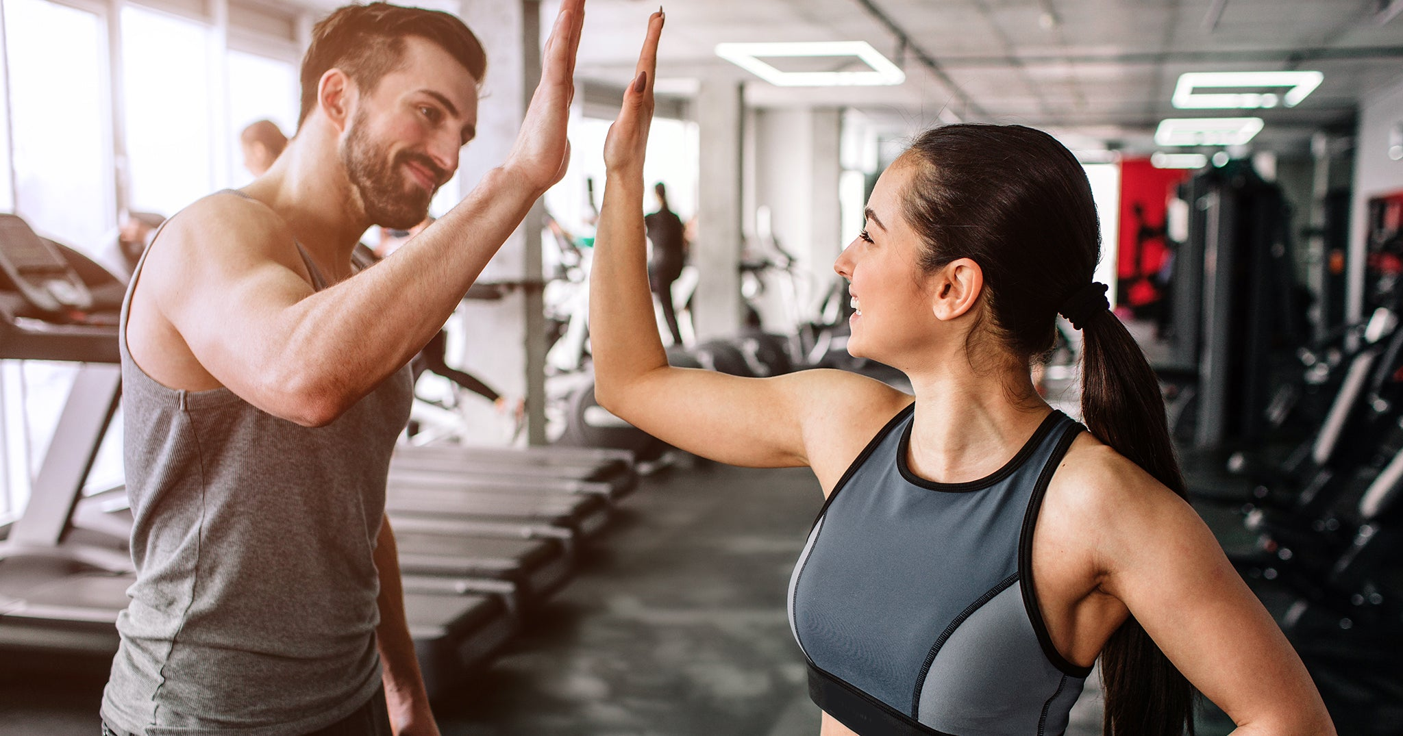 man woman in gym high-fiving