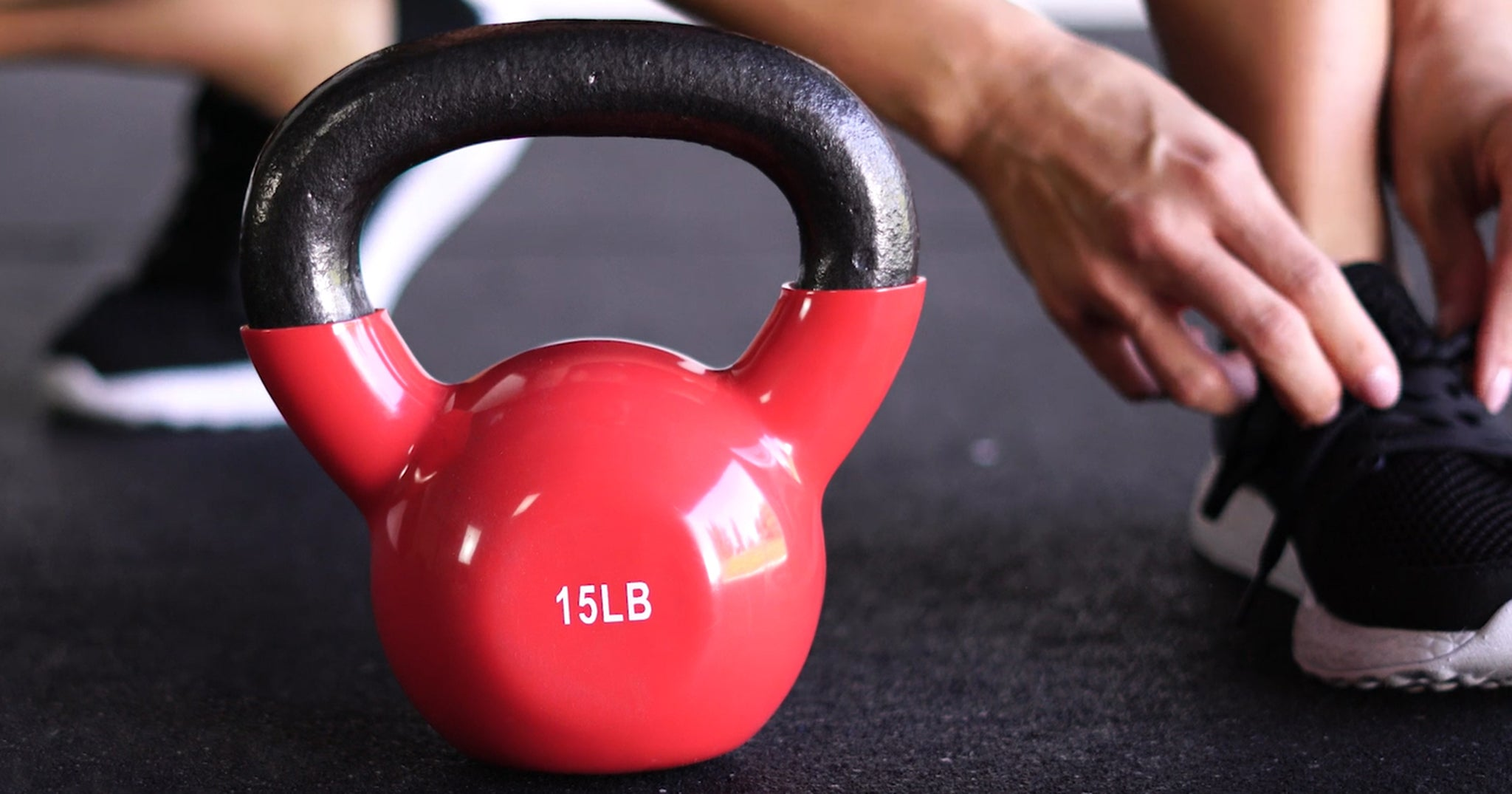 a red 15lb kettlebell and a person ties shoes