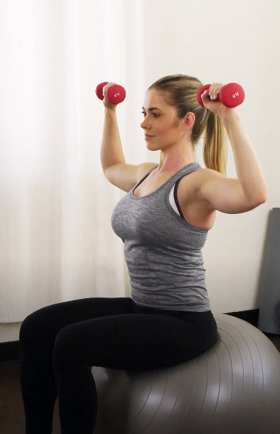woman sitting on gymball performing overhead press with dumbbells